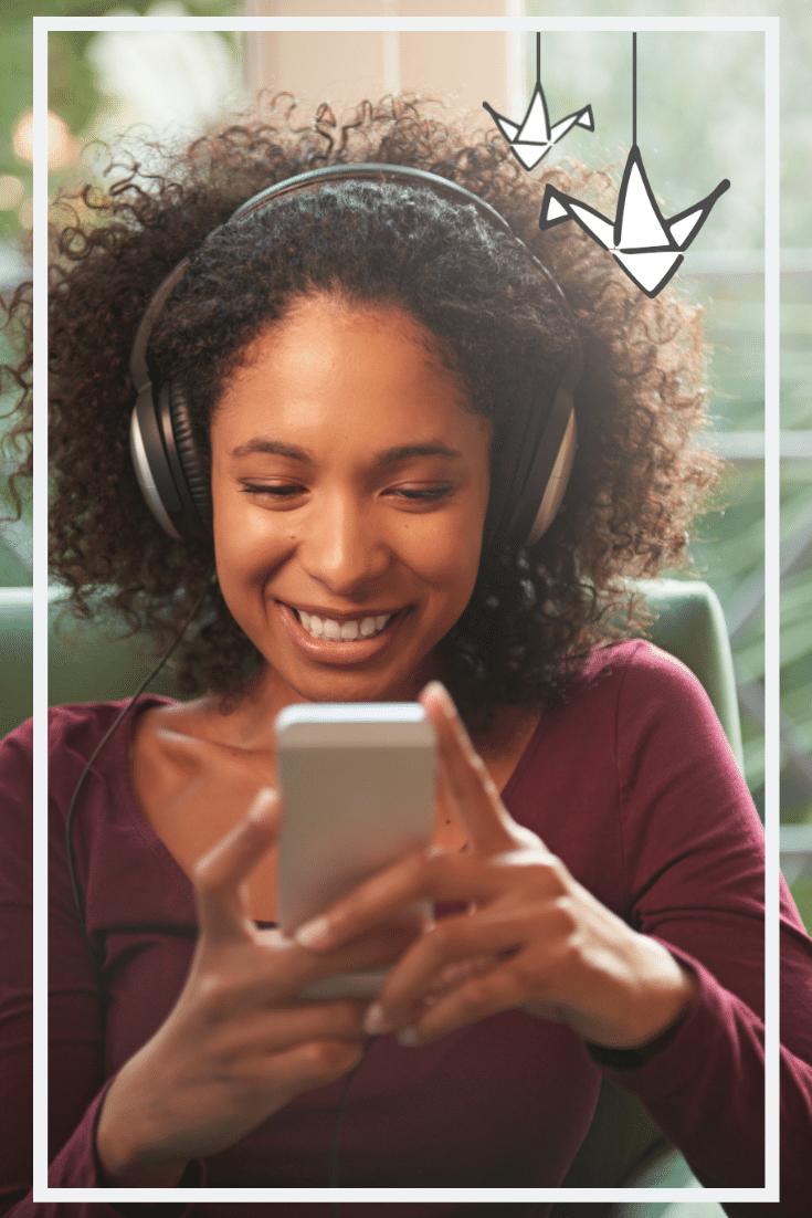 Person of Color, die mit Kopfhörern ein Smartphone in der Hand hält